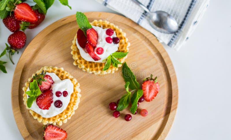 Οι εύγευστες βελγικές βάφλες με η κρέμα και οι φράουλες στο στρογγυλό ξύλινο πιάτο στοκ εικόνες