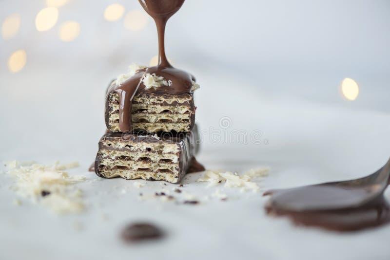 Οι εύγευστες γκοφρέτες με την έκχυση της σοκολάτας και της άσπρης σοκολάτας ψεκάζουν, κλείνουν επάνω, bokeh υπόβαθρο φω'των στοκ φωτογραφία