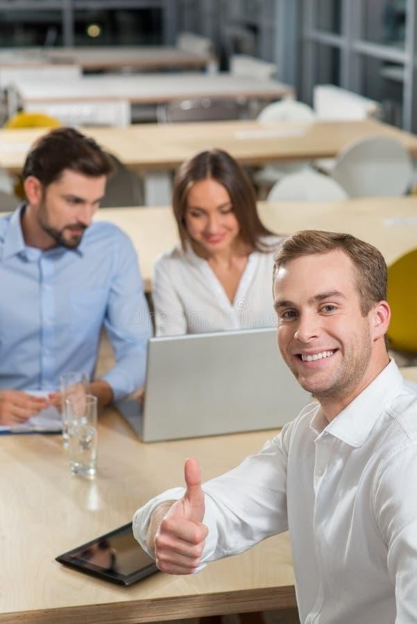 Οι εύθυμοι νέοι συνάδελφοι συζητούν την εργασία τους στοκ εικόνα με δικαίωμα ελεύθερης χρήσης