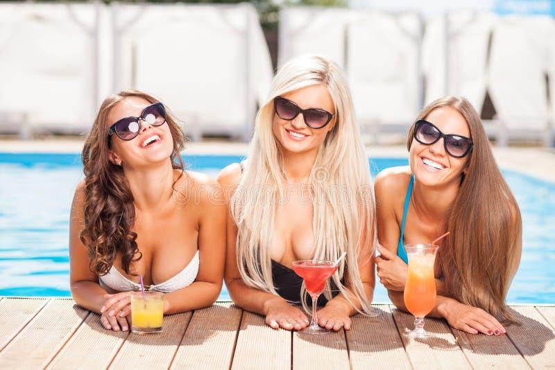 Οι ελκυστικές νέες γυναίκες απολαμβάνουν το ποτό στο νερό στοκ εικόνες