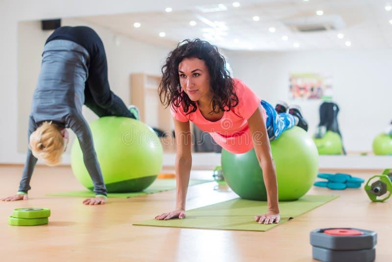 Οι ελκυστικές χαμογελώντας λεπτές νέες γυναίκες που εκπαιδεύουν στο εσωτερικό να κάνουν τους λούτσους κυλούν και handstand άσκηση στοκ εικόνες