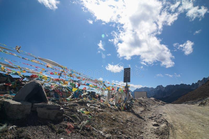 Οι ζωηρόχρωμες θιβετιανές σημαίες με το μπλε ουρανό στην άποψη δείχνουν κατά μήκος του δρόμου την επιφύλαξη φύσης Yading στοκ φωτογραφία με δικαίωμα ελεύθερης χρήσης