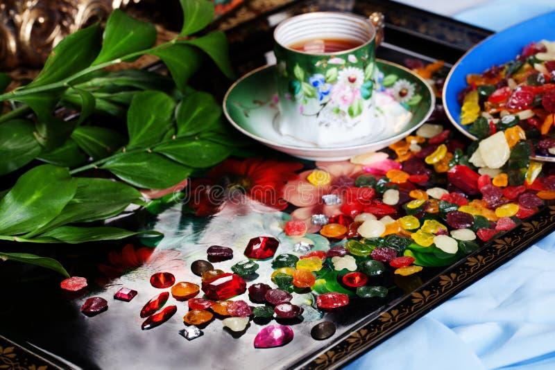 Οι ζωηρόχρωμες πτώσεις φρούτων καραμελών με τους πολύτιμους λίθους διασκόρπισαν σε έναν εορτασμό κόμματος τσαγιού δίσκων στοκ εικόνα με δικαίωμα ελεύθερης χρήσης