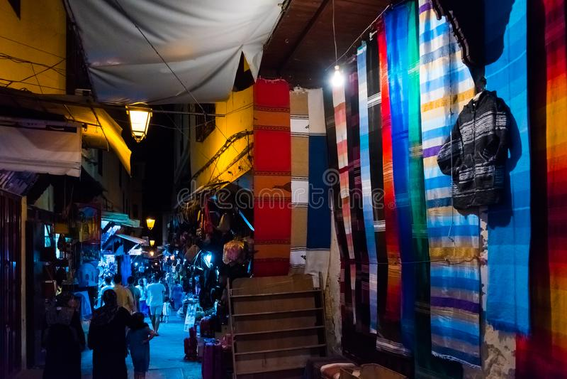 Οι ζωηρόχρωμες τέχνες ψωνίζουν με τους τάπητες και τις κουβέρτες σε μια παραδοσιακή μαροκινή αγορά στο medina του Fez, Μαρόκο, Αφ στοκ φωτογραφίες
