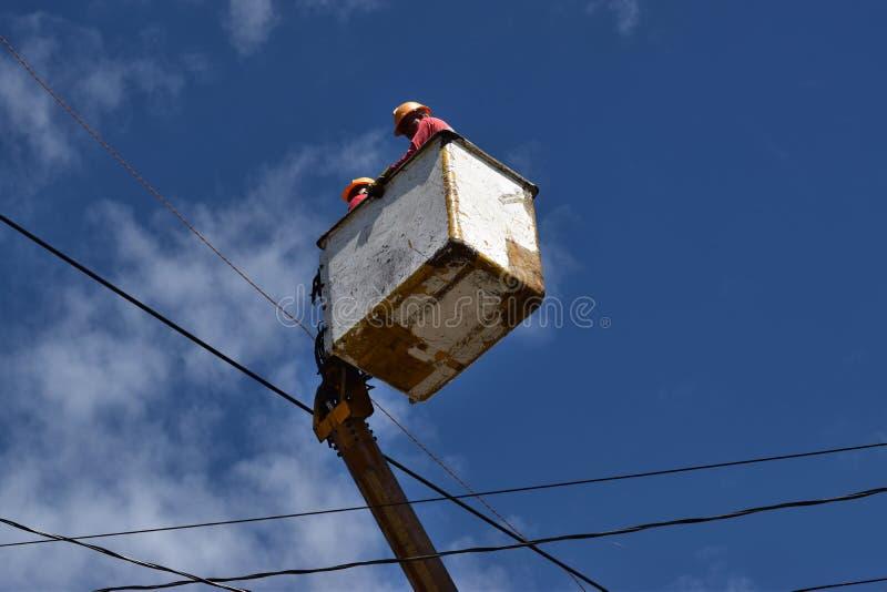 Οι ηλεκτρικοί εργαζόμενοι σε Telehandler με τον κάδο που εγκαθιστούν τα καλώδια υψηλής έντασης ψηλό συγκεκριμένο μετα Underside β στοκ εικόνα με δικαίωμα ελεύθερης χρήσης