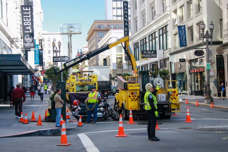 Οι δημοτικοί εργαζόμενοι κάνουν τη δραστηριότητα υπηρεσιών υποδομής πόλεων στη στο κέντρο της πόλης οδό στοκ εικόνα με δικαίωμα ελεύθερης χρήσης