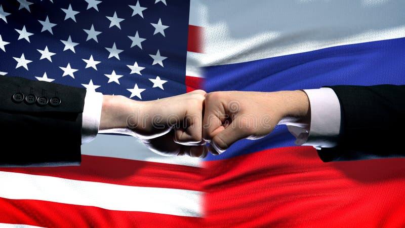 Οι ΗΠΑ εναντίον της Ρωσίας συγκρούονται, διεθνής κρίση σχέσεων, πυγμές στο υπόβαθρο σημαιών στοκ εικόνα με δικαίωμα ελεύθερης χρήσης