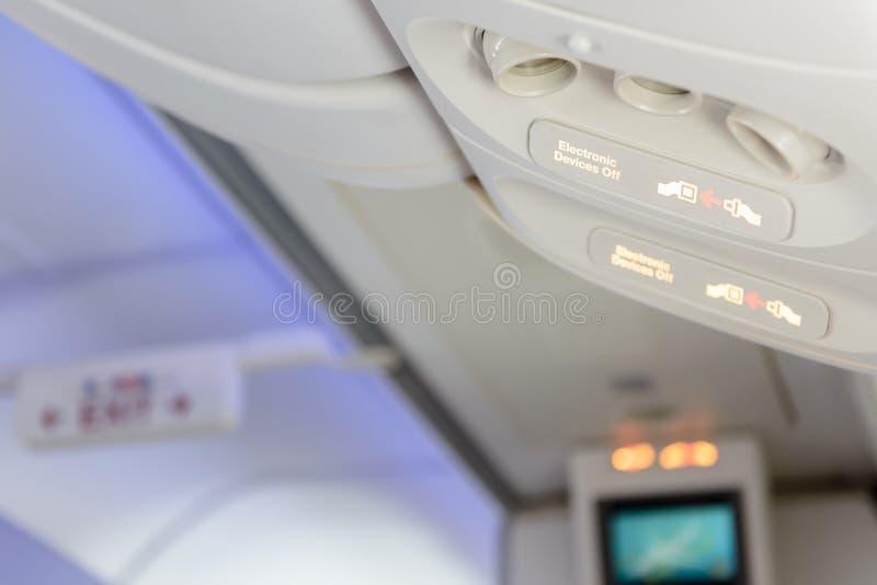 Οι ηλεκτρονικές συσκευές μακριά και στερεώνουν το σημάδι ζωνών ασφαλείας μέσα στο αεροπλάνο στοκ εικόνες με δικαίωμα ελεύθερης χρήσης