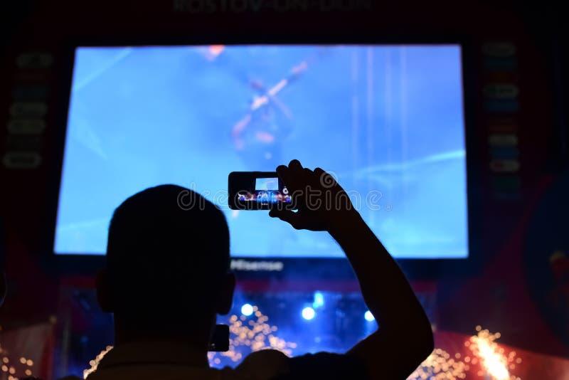 Οι θαυμαστές απολαμβάνουν τη συναυλία στη ζώνη ανεμιστήρων της αίθουσας κατά τη διάρκεια της συναυλίας πλήθος των σκιαγραφιών ανθ στοκ φωτογραφία με δικαίωμα ελεύθερης χρήσης