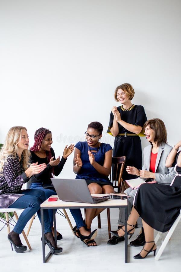 Οι θετικές γυναίκες συζητούν το σχέδιο οργάνωσης καθμένος στον πίνακα με το lap-top στοκ εικόνες
