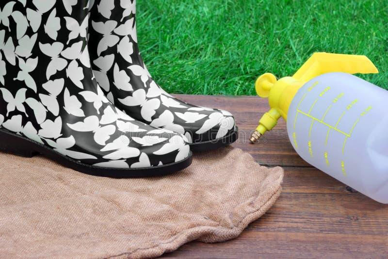 Οι θηλυκές λαστιχένιες μπότες και το πότισμα μπορούν στο ξύλινο γραφείο στοκ εικόνες