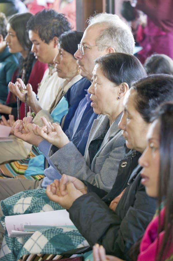 Οι θιασώτες κρατούν τις χάντρες και το ρύζι προσευχής κατά τη διάρκεια μιας ενδυνάμωσης Amitabha που η βουδιστική τελετή, περισυλ στοκ εικόνα