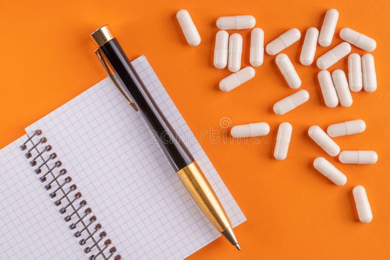 Οι ιατρικά κάψες και τα χάπια γύρω από το κενό σημειωματάριο με τη μάνδρα στο πορτοκαλί υπόβαθρο, κλείνουν επάνω στοκ εικόνα