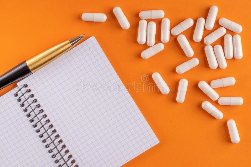 Οι ιατρικά κάψες και τα χάπια γύρω από το κενό σημειωματάριο με τη μάνδρα στο πορτοκαλί υπόβαθρο, κλείνουν επάνω στοκ εικόνες