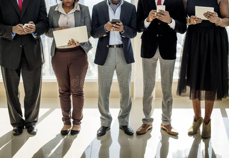 Οι διαφορετικοί επιχειρηματίες χρησιμοποιούν τις ψηφιακές συσκευές στοκ εικόνα με δικαίωμα ελεύθερης χρήσης