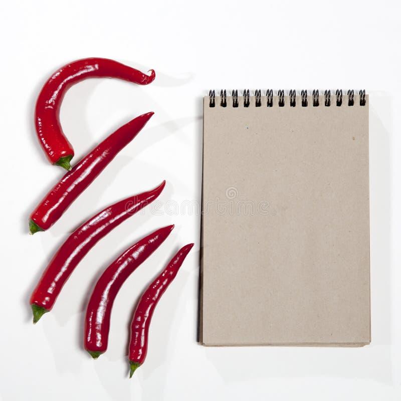 Οι κάρτες για τις συνταγές Sketchpad και κόκκινο - καυτό πιπέρι ως πλαίσιο σε ένα άσπρο υπόβαθρο στοκ εικόνες