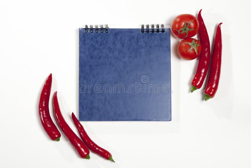 Οι κάρτες για τις συνταγές Sketchpad και το κόκκινο - καυτό πιπέρι ως πλαίσιο σε ένα άσπρο υπόβαθρο στοκ εικόνα