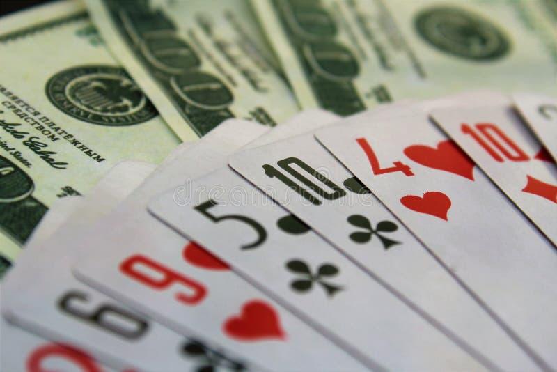 Οι κάρτες παιχνιδιού και τα δολάρια χρημάτων διαδίδονται έξω στον πίνακα στοκ εικόνα με δικαίωμα ελεύθερης χρήσης