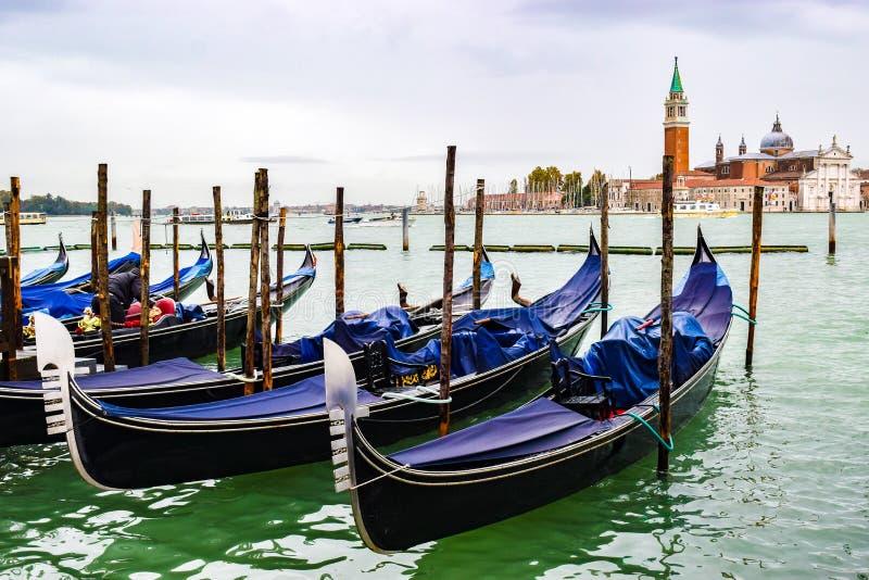 Οι καλυμμένες γόνδολες ελλιμένισαν στο νερό μεταξύ των ξύλινων πόλων πρόσδεσης στη Βενετία, Ιταλία Εκκλησία του SAN Giorgio Maggi στοκ φωτογραφίες με δικαίωμα ελεύθερης χρήσης