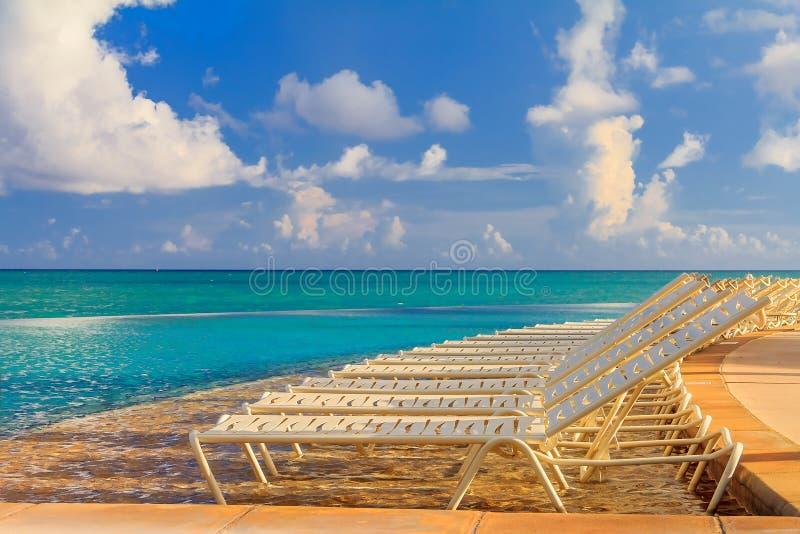 Οι καρέκλες λιμνών από το τυρκουάζ ποτίζουν σε μια τροπική παραλία και ένα poo στοκ εικόνες με δικαίωμα ελεύθερης χρήσης