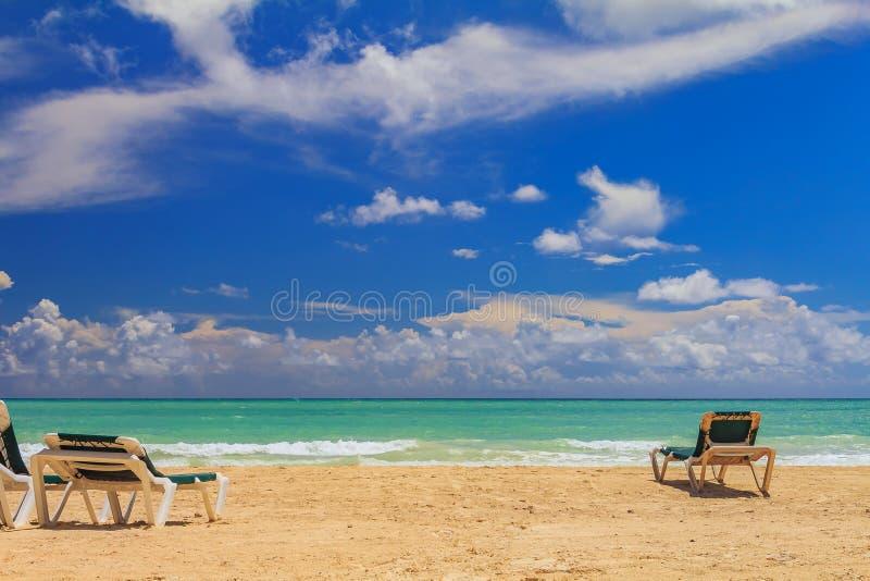 Οι καρέκλες παραλιών από το τυρκουάζ ποτίζουν σε μια τροπική παραλία στο Γ στοκ φωτογραφίες