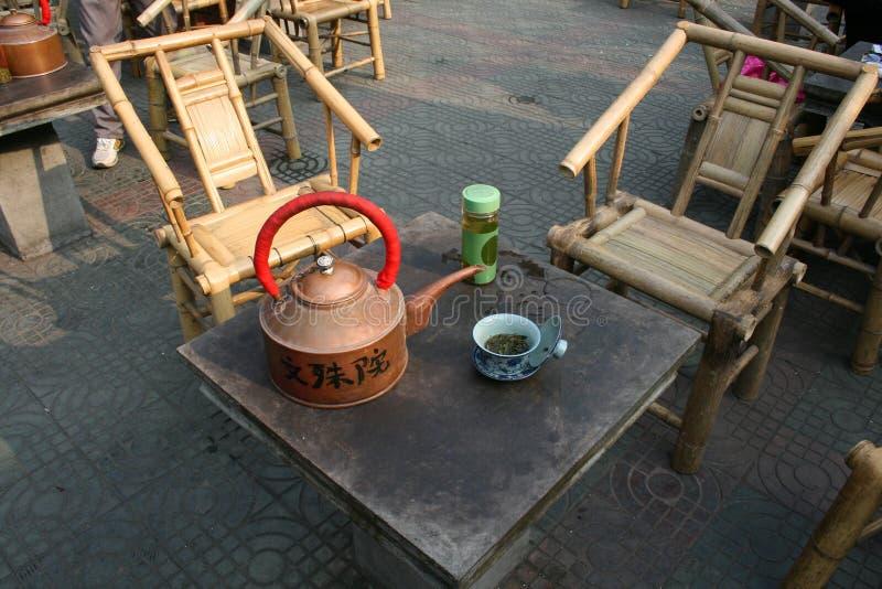 Οι καρέκλες μπαμπού αναμένουν τους προστάτες για να πιουν το κινεζικό πράσινο τσάι από το δοχείο χαλκού στοκ εικόνες