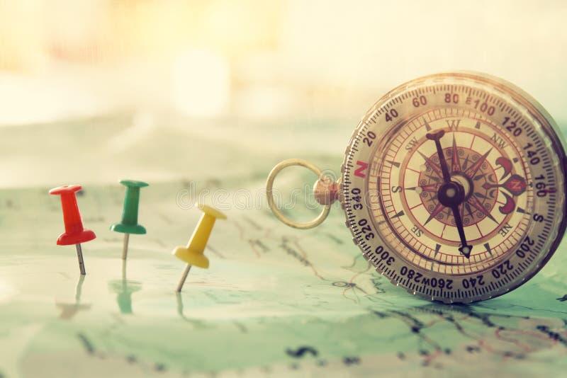 οι καρφίτσες συνδέθηκαν με το χάρτη, που παρουσιάζει τον προορισμό θέσης ή ταξιδιού και παλαιά πυξίδα στοκ εικόνα