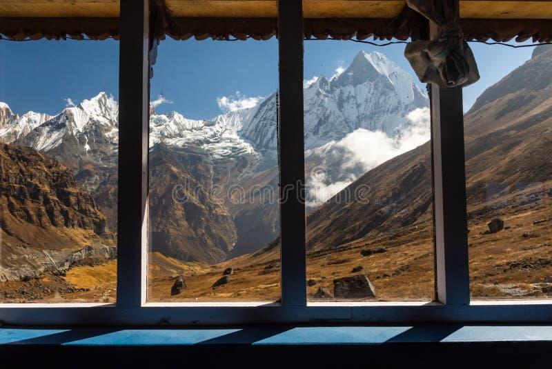 Οι καταπληκτικές απόψεις μέσω του γυαλιού παραθύρων της ουράς Machapuchare ψαριών στο Annapurna κυμαίνονται, Ιμαλάια στοκ φωτογραφία