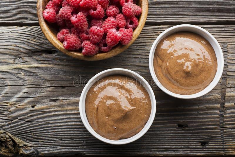 Οι καταφερτζήδες μπανανών σοκολάτας εξυπηρέτησαν τα φρέσκα juicy ώριμα σμέουρα με ένα κλαδάκι της μέντας στα portioned κύπελλα σε στοκ εικόνα με δικαίωμα ελεύθερης χρήσης