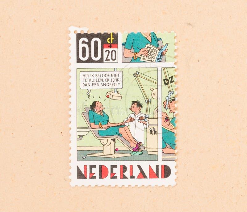 ΟΙ ΚΑΤΩ ΧΏΡΕΣ 1980: Ένα γραμματόσημο που τυπώνεται στις Κάτω Χώρες παρουσιάζει ένα σχέδιο ενός ασθενή και ενός οδοντιάτρου, circa στοκ εικόνες με δικαίωμα ελεύθερης χρήσης