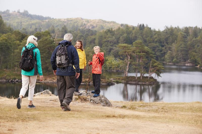 Οι καυκάσιοι παππούδες και γιαγιάδες περπατούν στα εγγόνια τους για να θαυμάσουν την άποψη όχθεων της λίμνης, πίσω άποψη, περιοχή στοκ εικόνα