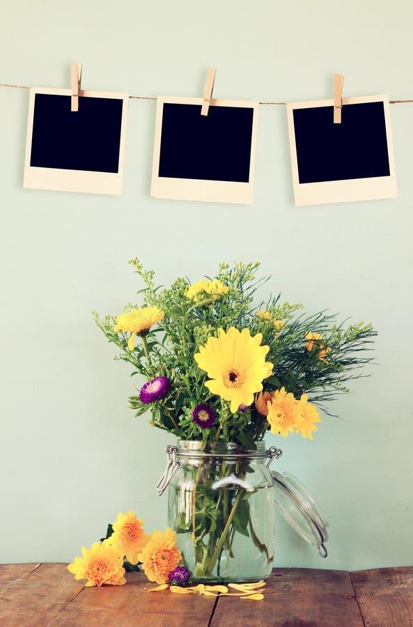 Οι κενές κενές στιγμιαίες φωτογραφίες κρεμούν σε ένα σχοινί πέρα από τη θερινή ανθοδέσμη των λουλουδιών στον ξύλινο πίνακα με το  στοκ φωτογραφίες