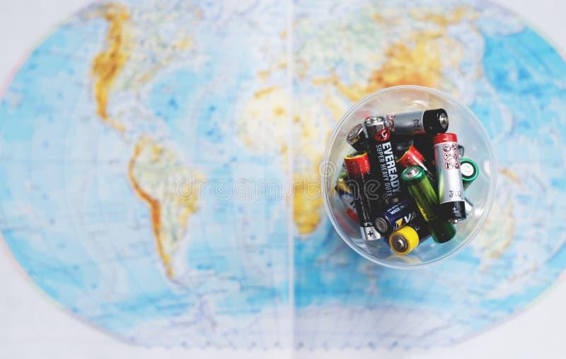 Οι κενές μίας χρήσης μπαταρίες στην πλαστική ΚΑΠ Χάρτης του κόσμου ως θολωμένο υπόβαθρο _χαμηλός βάθος ο Filed στοκ εικόνες