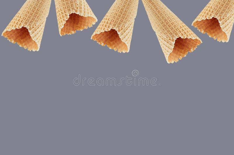 Οι κενοί κώνοι παγωτού βαφλών ως διακοσμητικό πλαίσιο στο γκρίζο υπόβαθρο, χλευάζουν επάνω για τη διαφήμιση, σχέδιο, επιλογές στοκ φωτογραφία