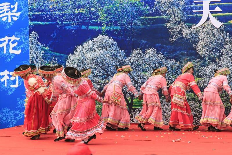 Οι κινεζικές γυναίκες έντυσαν με τον παραδοσιακό ιματισμό που χορεύει και που τραγουδά κατά τη διάρκεια του φεστιβάλ λουλουδιών α στοκ εικόνες