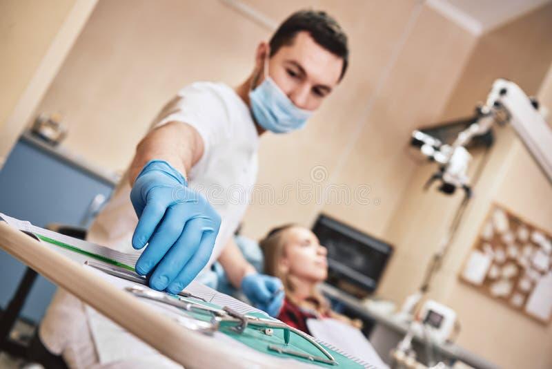 Οι κοιλότητες don't μας φοβίζουν! Έφηβος στο οδοντικό γραφείο Ο οδοντίατρος μεταχειρίζεται τα δόντια, κορίτσι που βρίσκεται στη στοκ εικόνα