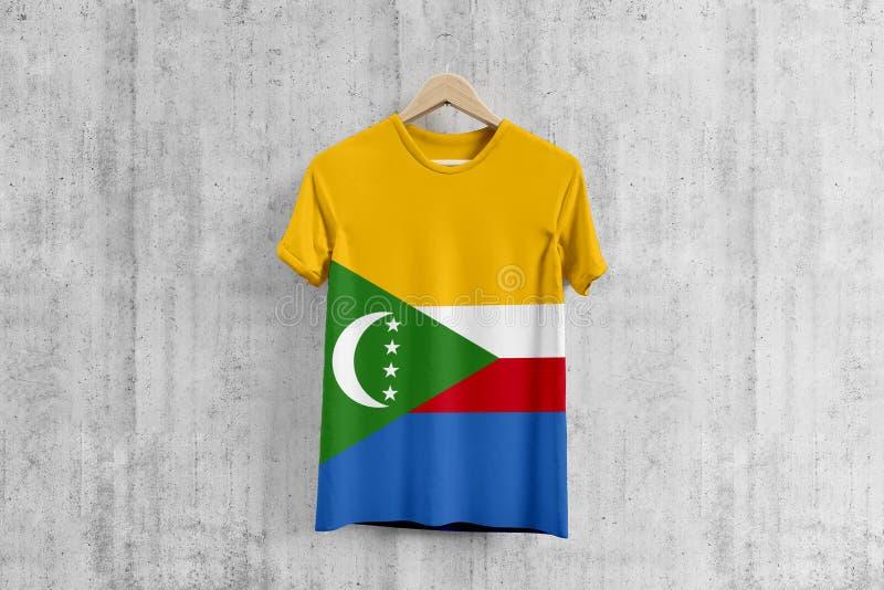 Οι Κομόρες σημαιοστολίζουν την μπλούζα στην κρεμάστρα, ομοιόμορφη ιδέα σχεδίου ομάδων Comoran για την παραγωγή ενδυμάτων Εθνική έ ελεύθερη απεικόνιση δικαιώματος