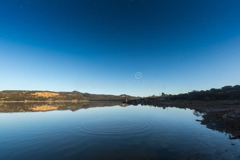 Οι κυματισμοί σε μια λίμνη στην ανατολή με το αστέρι γέμισαν το βαθύ μπλε ουρανό στοκ φωτογραφία