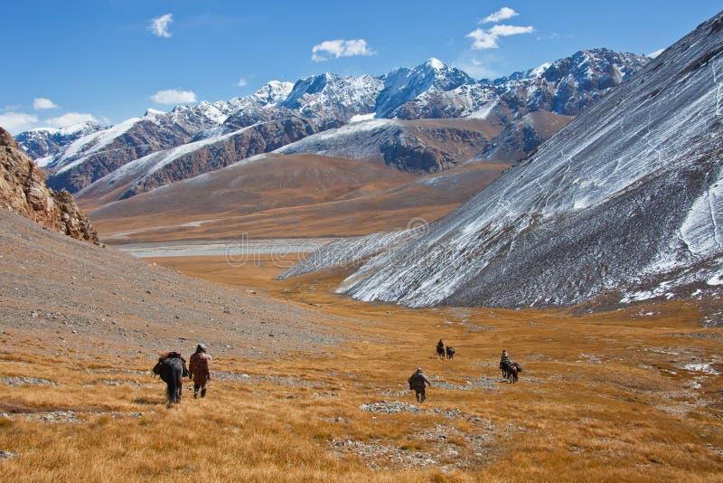 Οι κυνηγοί με τα άλογα κατεβαίνουν από τα βουνά στην κοιλάδα στοκ εικόνα
