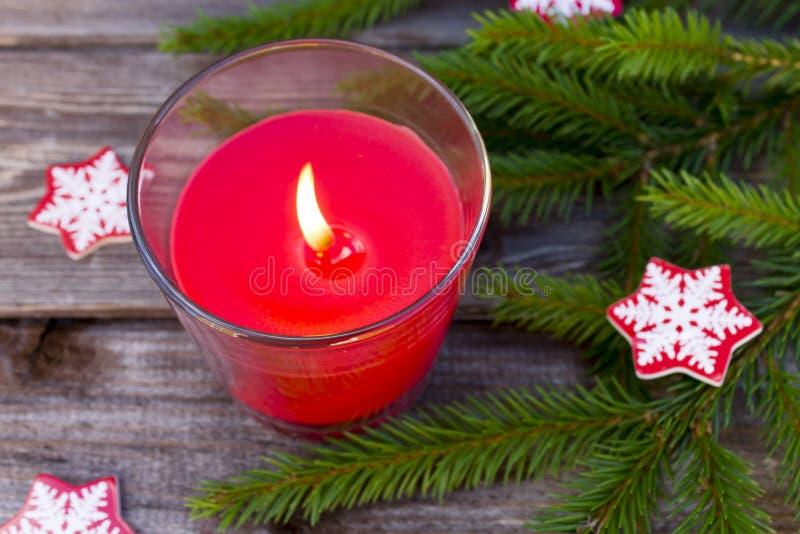 Οι κόκκινα διακοσμήσεις και το έλατο κεριών Χριστουγέννων διακλαδίζονται στο εκλεκτής ποιότητας ξύλινο υπόβαθρο πινάκων με το διά στοκ εικόνα με δικαίωμα ελεύθερης χρήσης