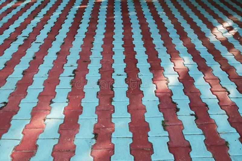 Οι κόκκινες και μπλε γραμμές φιαγμένες από συγκεκριμένα πεζοδρόμια, χρωματισμένο υπόβαθρο με την εξαφάνιση δείχνουν στοκ εικόνες
