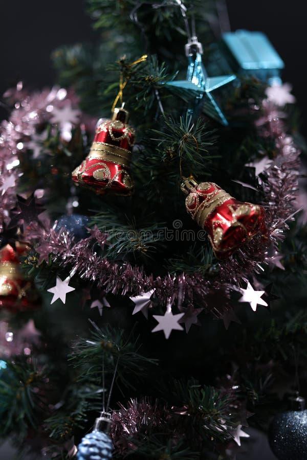 Οι κόκκινες και μπλε διακοσμήσεις Χριστούγεννο-δέντρων που κρεμούν στους κλάδους μεταξύ λαμπρό tinsel στοκ εικόνες