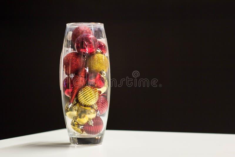 Οι κόκκινες και χρυσές διακοσμήσεις σφαιρών Χριστουγέννων τοποθετούνται σε ένα βάζο γυαλιού ως επιτραπέζιο διακοσμητικό κομμάτι στοκ εικόνες