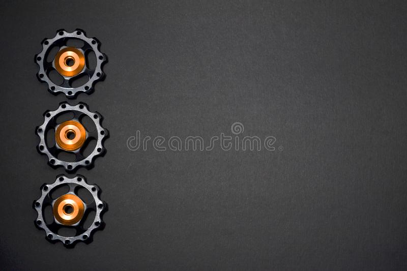 Οι κύλινδροι χρώματος, μαύρα, χρυσά εργαλεία για το ποδήλατο εκτρέφουν το derailleur στο γκρίζο υπόβαθρο στη αριστερή πλευρά, με  στοκ εικόνες