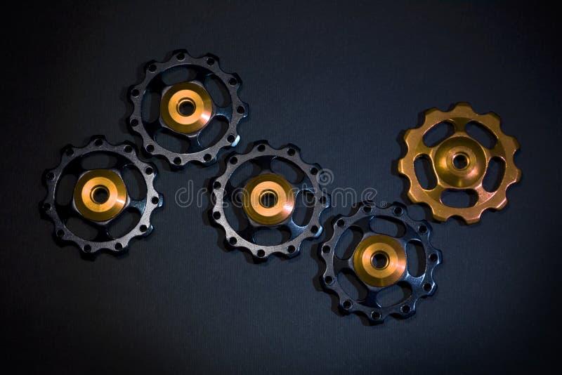 Οι κύλινδροι χρώματος, μαύρα, χρυσά εργαλεία για το ποδήλατο εκτρέφουν το derailleur στο μαύρο υπόβαθρο στοκ φωτογραφία με δικαίωμα ελεύθερης χρήσης