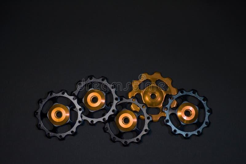 Οι κύλινδροι χρώματος, μαύρα, χρυσά εργαλεία για το ποδήλατο εκτρέφουν το derailleur στο μαύρο υπόβαθρο στην κατώτατη πλευρά, με  στοκ εικόνες
