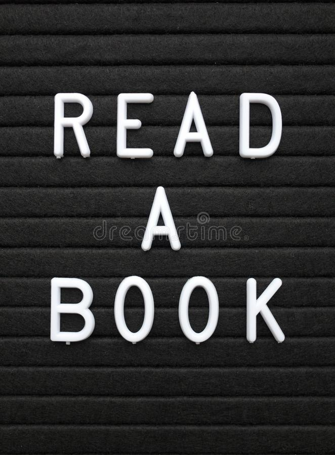 Οι λέξεις διαβάζουν ένα βιβλίο στο άσπρο κείμενο σε έναν μαύρο πίνακα επιστολών στοκ φωτογραφία