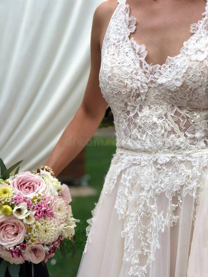 Οι λεπτομέρειες ενός γαμήλιου φορέματος, νύφη κρατούν μια weding ανθοδέσμη στοκ εικόνα