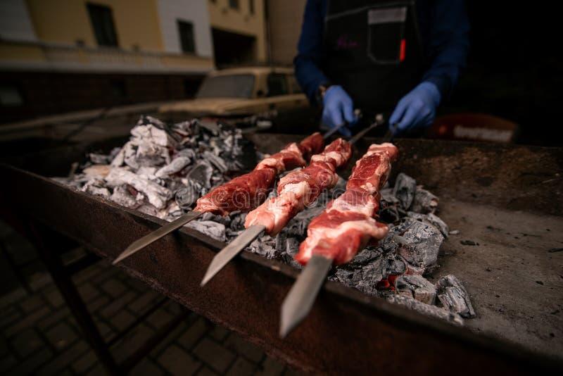 Οι μάγειρες χεριών στα μπλε γάντια κρατούν τα οβελίδια με το κρέας στη σχάρα στοκ φωτογραφία με δικαίωμα ελεύθερης χρήσης