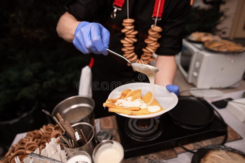 Οι μάγειρες χεριών στην μπλε λαβή γαντιών κρατούν ένα πιάτο των τηγανιτών στοκ φωτογραφία